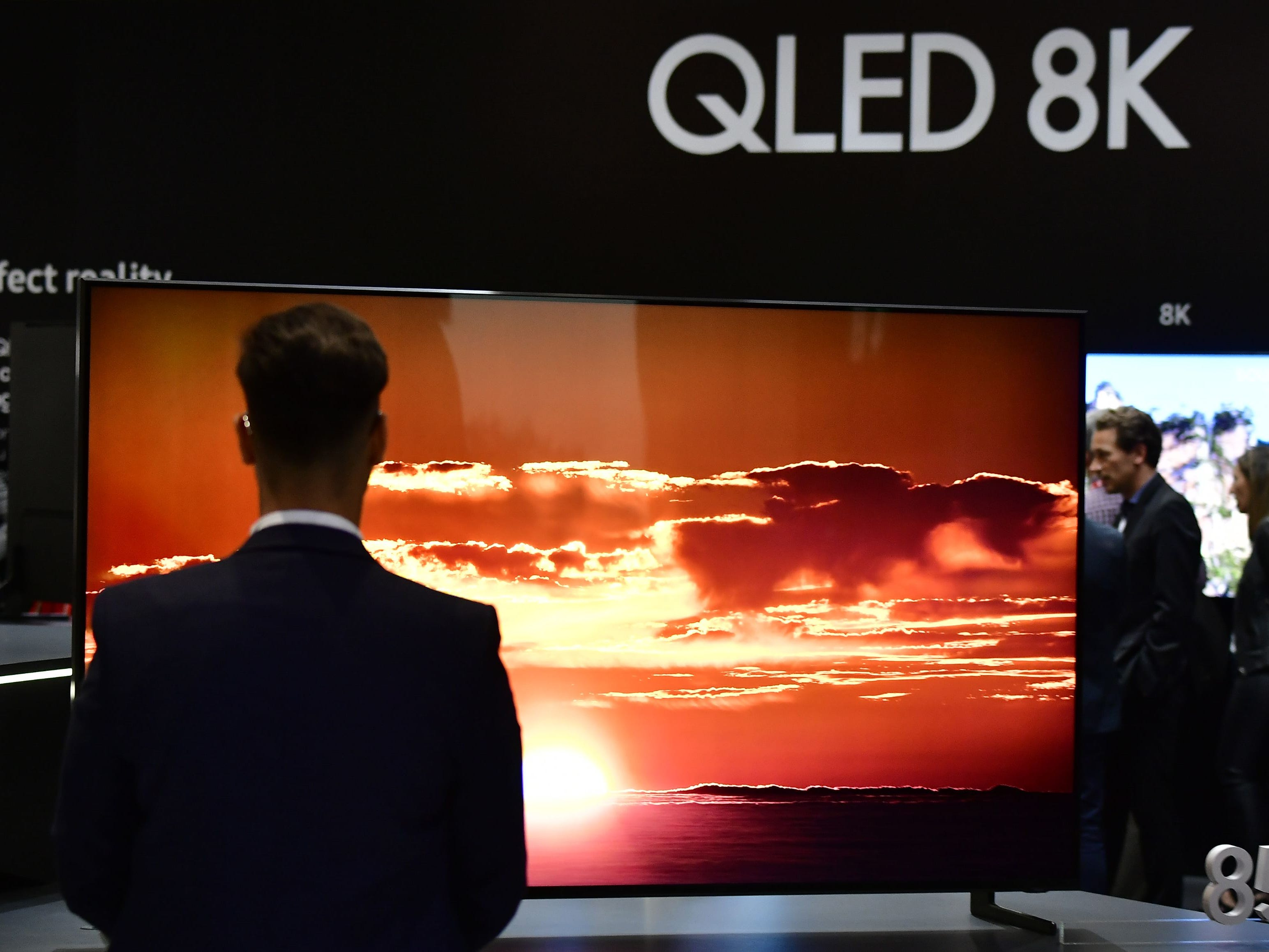 Visitors look at a television installation at the booth of Samsung during a preview day for the IFA, the world's leading trade show for consumer electronics and home appliances, in Berlin on August 30, 2018. (Photo by Tobias SCHWARZ / AFP)TOBIAS SCHWARZ/AFP/Getty Images ORIG FILE ID: AFP_18P7E2