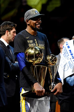 Golden State Warriors forward Kevin Durant (35) celebrates with the Bill Russell NBA Finals Most Valuable Player Award and the Larry O'Brien Championship Trophy after beating the Cleveland Cavaliers in game four of the 2018 NBA Finals at Quicken Loans Arena.