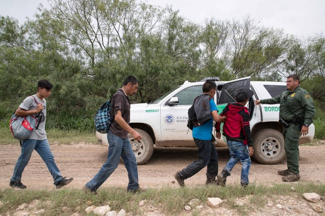 A group of migrant families walk down a dirt road after being intercepted by Border Patrol near McAllen, Texas, on June 19, 2018.
