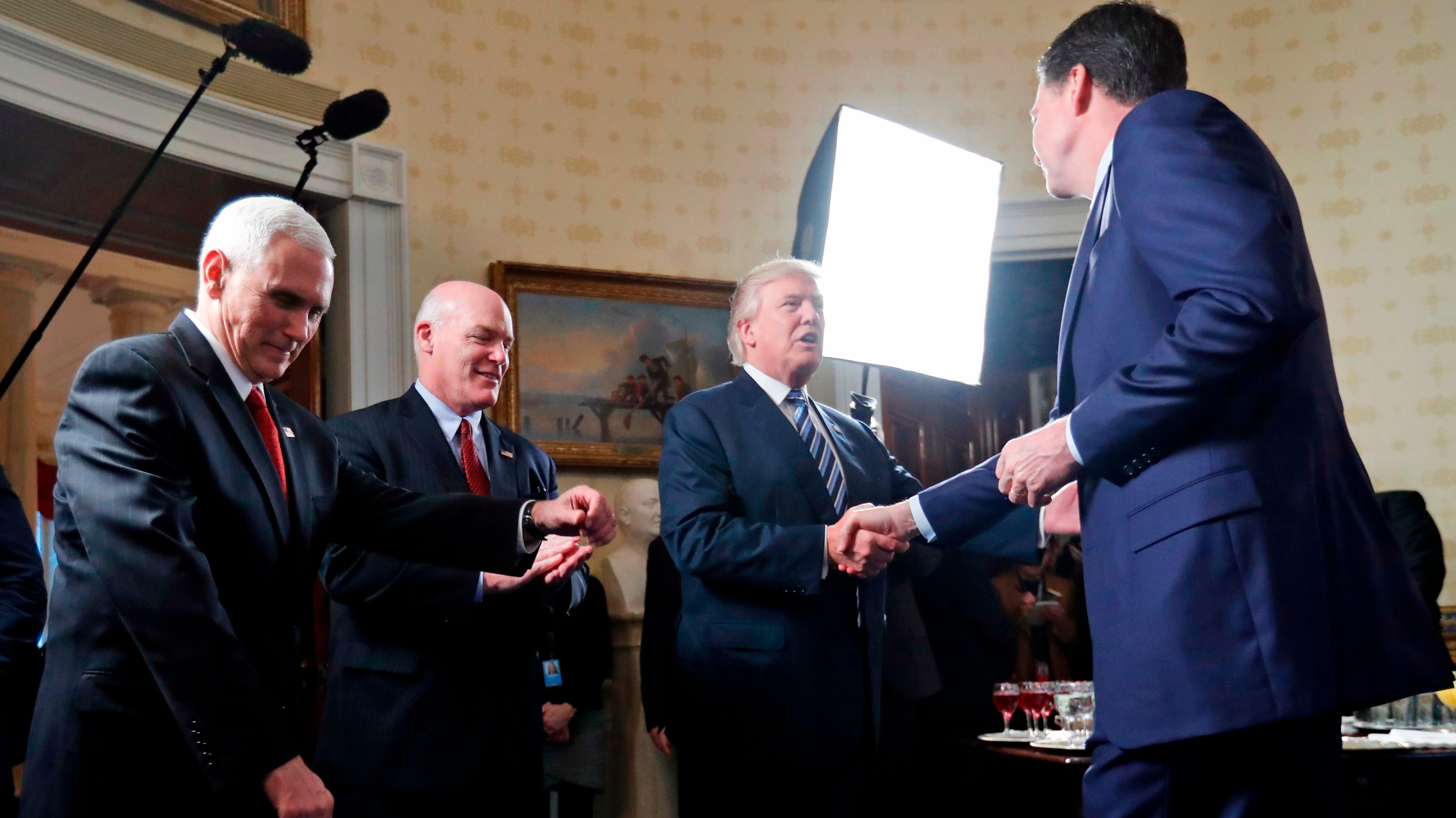President Donald Trump shakes hands Jan. 22, 2017, with then-FBI Director James Comey during an event for first responders in the Blue Room of the White House. Vice President Mike Pence, left, and Secret Service Director Joseph Clancy also attended.