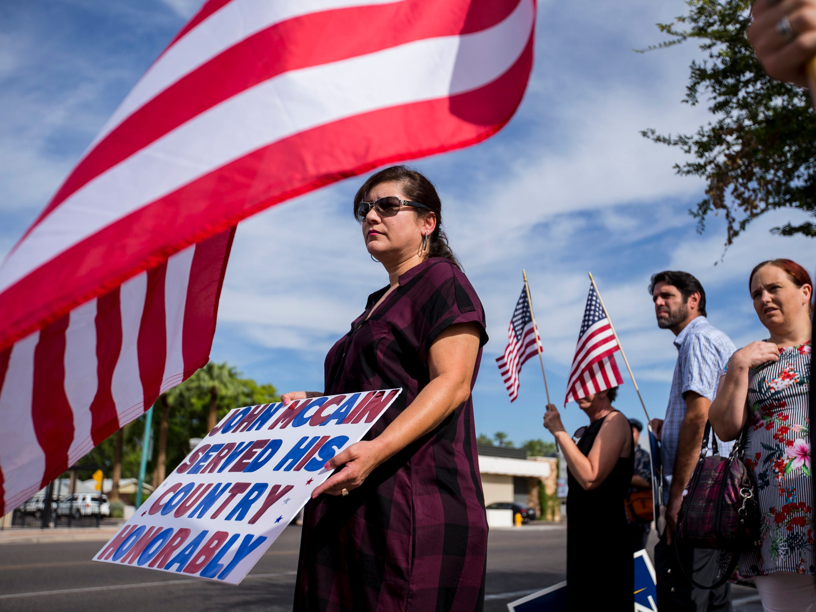 Melissa Arvizo holds a sign for Sen. John McCain along the motorcade route to a memorial service for McCain, Aug. 30, 2018, in Phoenix.
