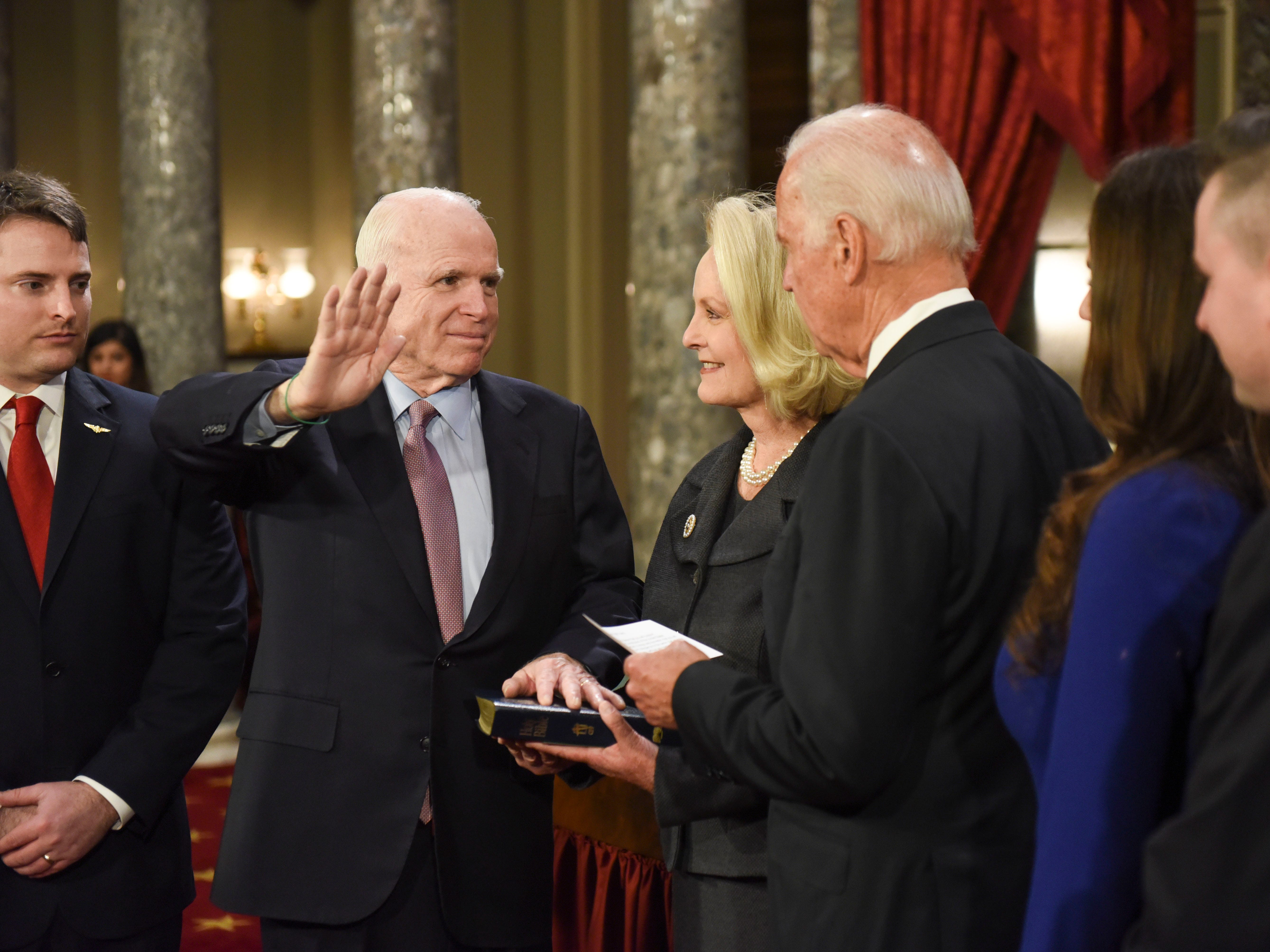 Vice President Joe Biden administers the Senate oath of office to Sen. John McCain, R-Ariz., accompanied by his wife, Cindy McCain, holding bible, and his family look on during a a mock swearing in ceremony in the Old Senate Chamber on Capitol Hill in Washington, Tuesday, Jan. 3, 2017. (AP Photo/Kevin Wolf)