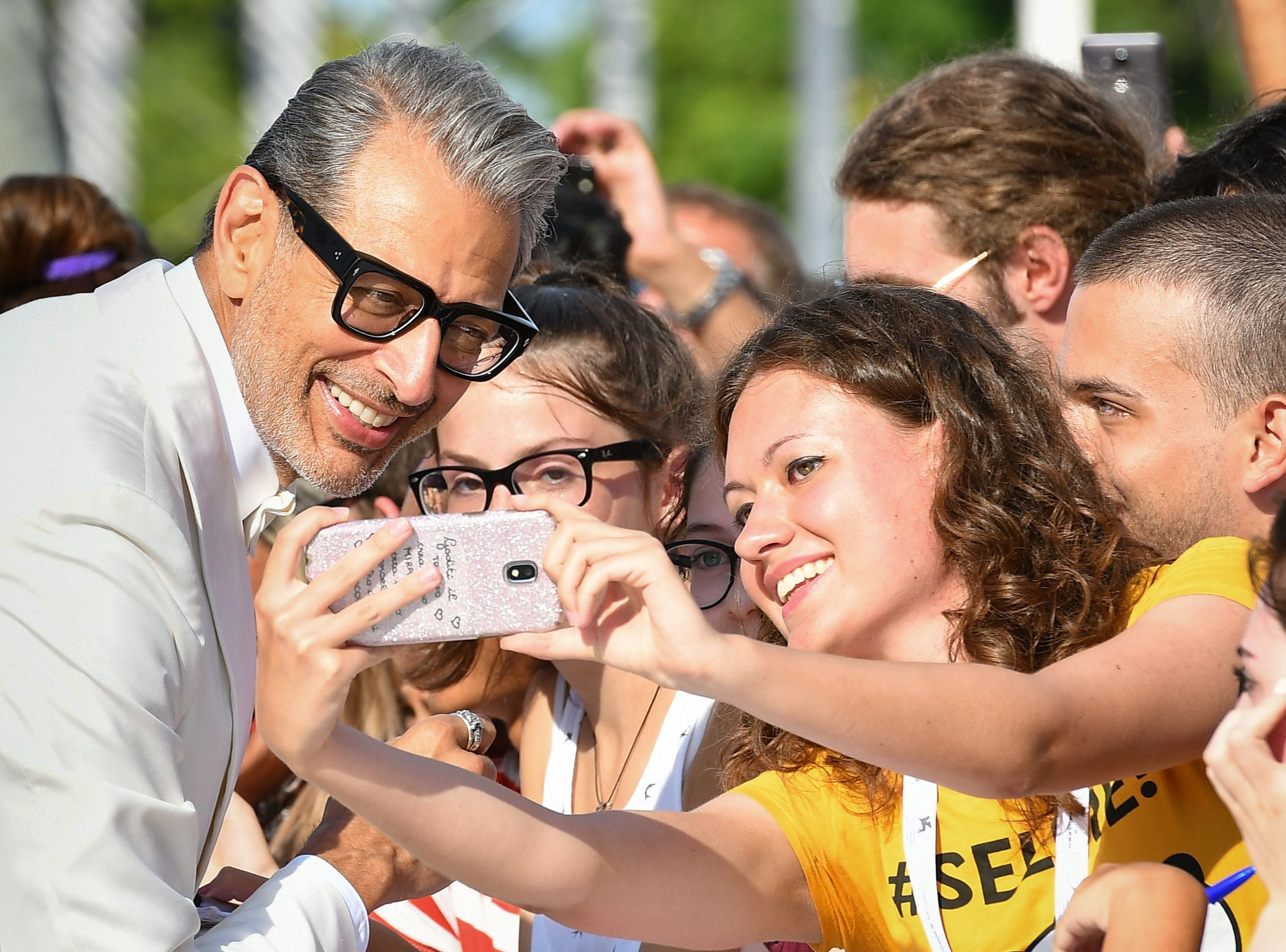 """Actor Jeff Goldblum poses for a selfie photo with a fan as he arrives for the premiere of the film """"The Mountain"""" presented in competition on August 30, 2018 during the 75th Venice Film Festival at Venice Lido. (Photo by Vincenzo PINTO / AFP)VINCENZO PINTO/AFP/Getty Images ORIG FILE ID: AFP_18P9ML"""