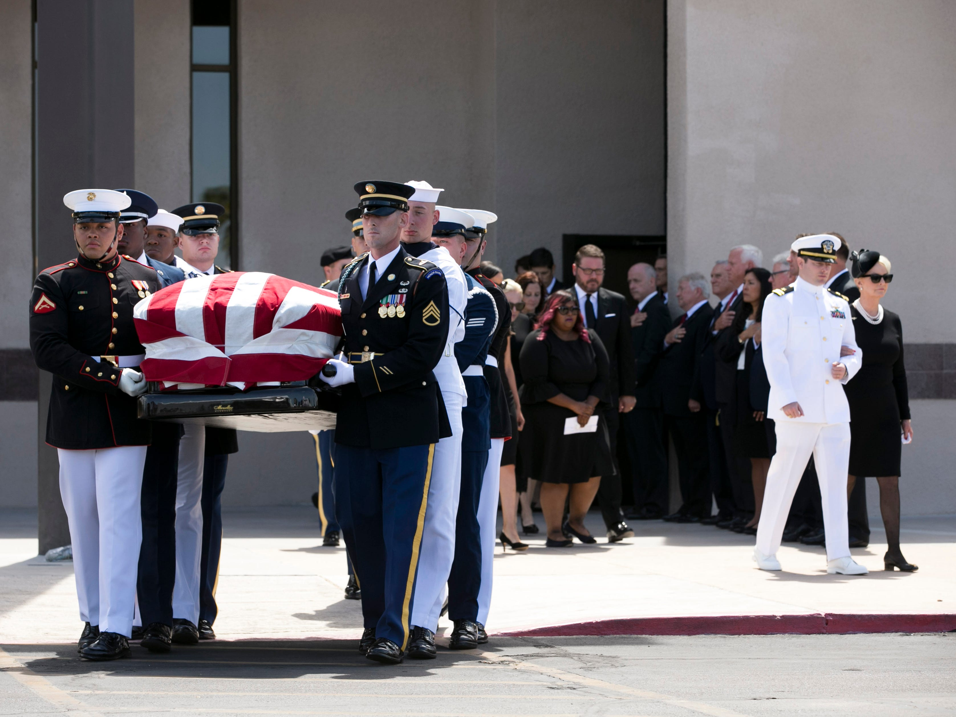 Members of the United States military carry the flag draped casket of Sen. John McCain out of North Phoenix Baptist Church as Jack McCain, right, escorts his mother, Cindy McCain, out of the church following a memorial service, Aug. 30, 2018, in Phoenix.