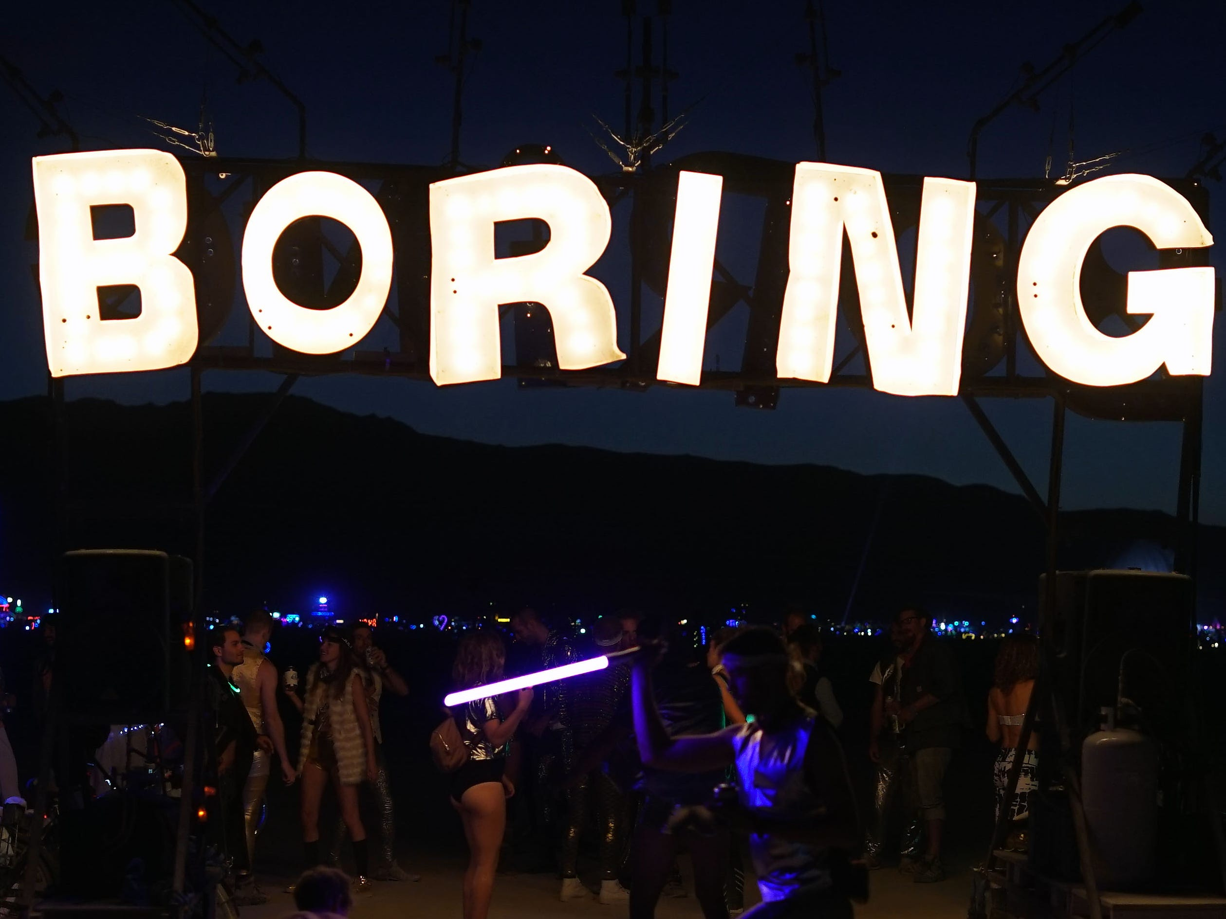 Dancers enjoy Burning Man beneath a sign cautioning them to stay focused.
