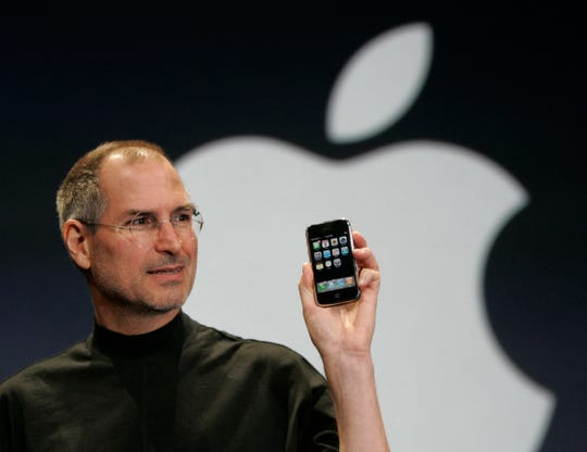 In this Jan. 9, 2007, file photo, Apple CEO Steve Jobs holds up the new iPhone.