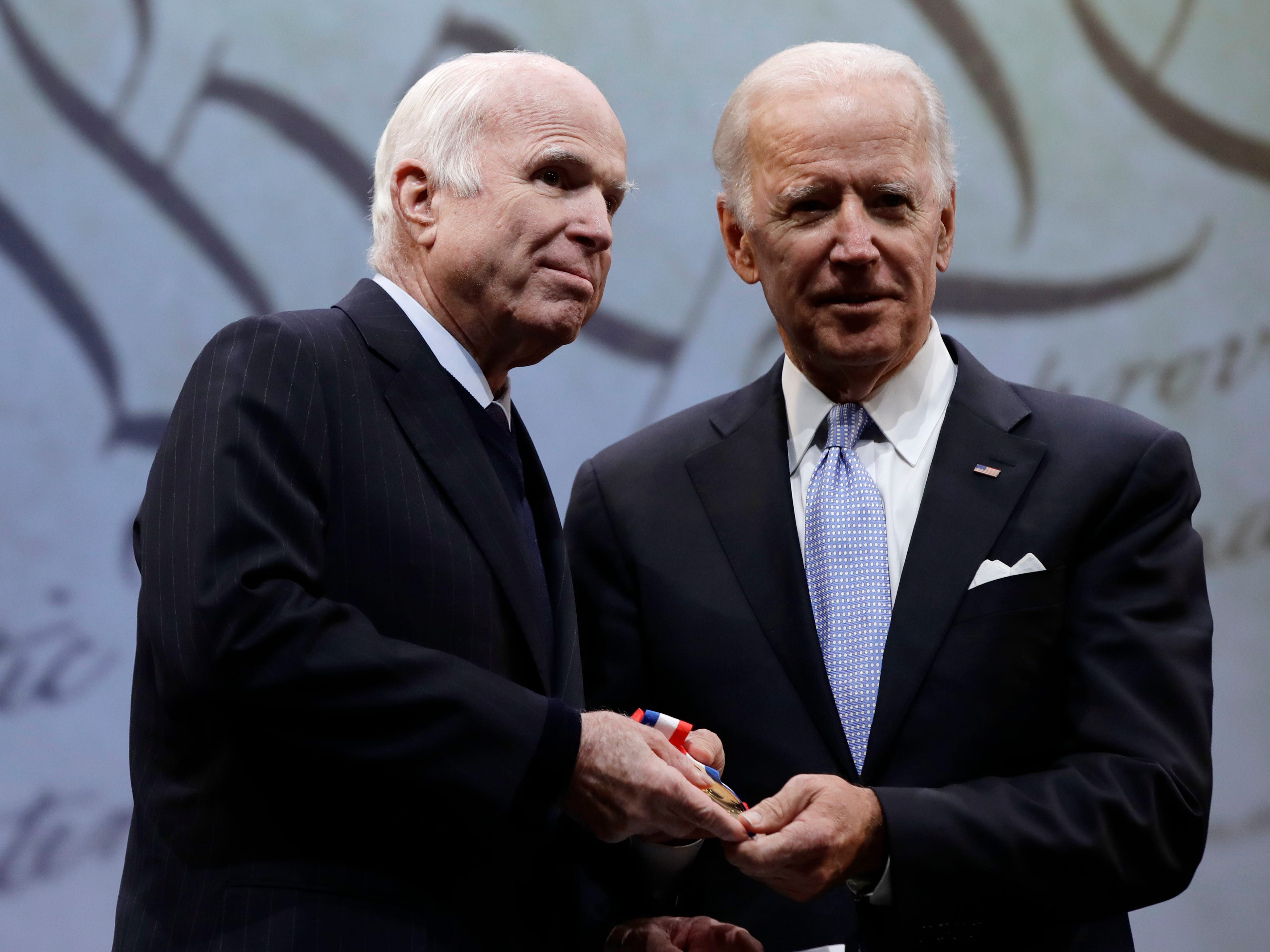 Sen. John McCain, R-Ariz., receives the Liberty Medal from Chair of the National Constitution Center's Board of Trustees, former Vice President Joe Biden in Philadelphia, Monday, Oct. 16, 2017. The honor is given annually to an individual who displays courage and conviction while striving to secure liberty for people worldwide. (AP Photo/Matt Rourke)