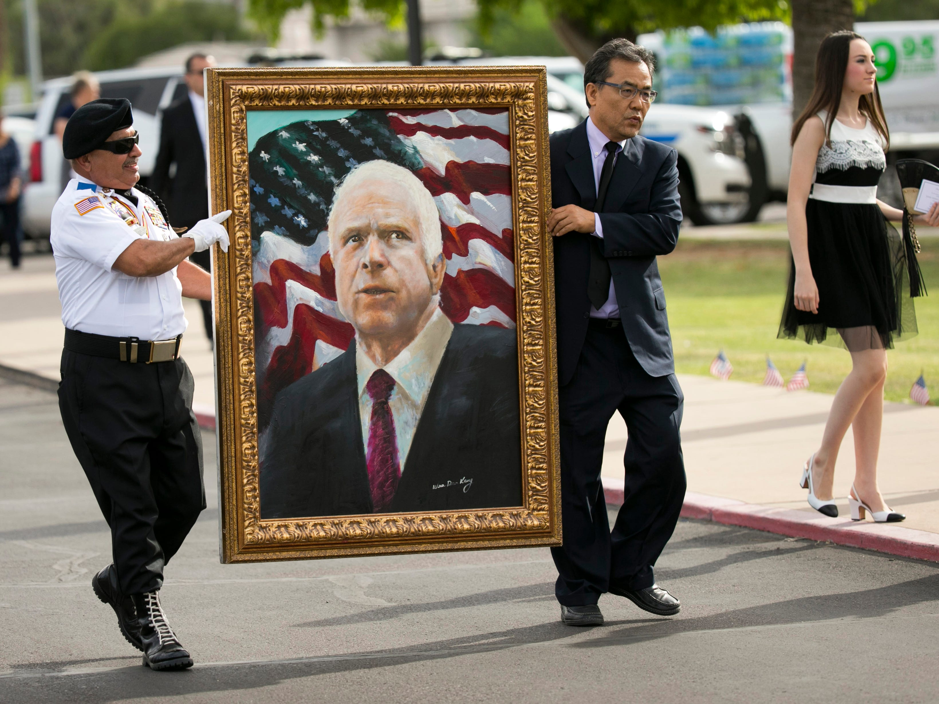 A portrait of Sen. John McCain is carried to North Phoenix Baptist Church before a memorial service, Aug. 30, 2018, in Phoenix.