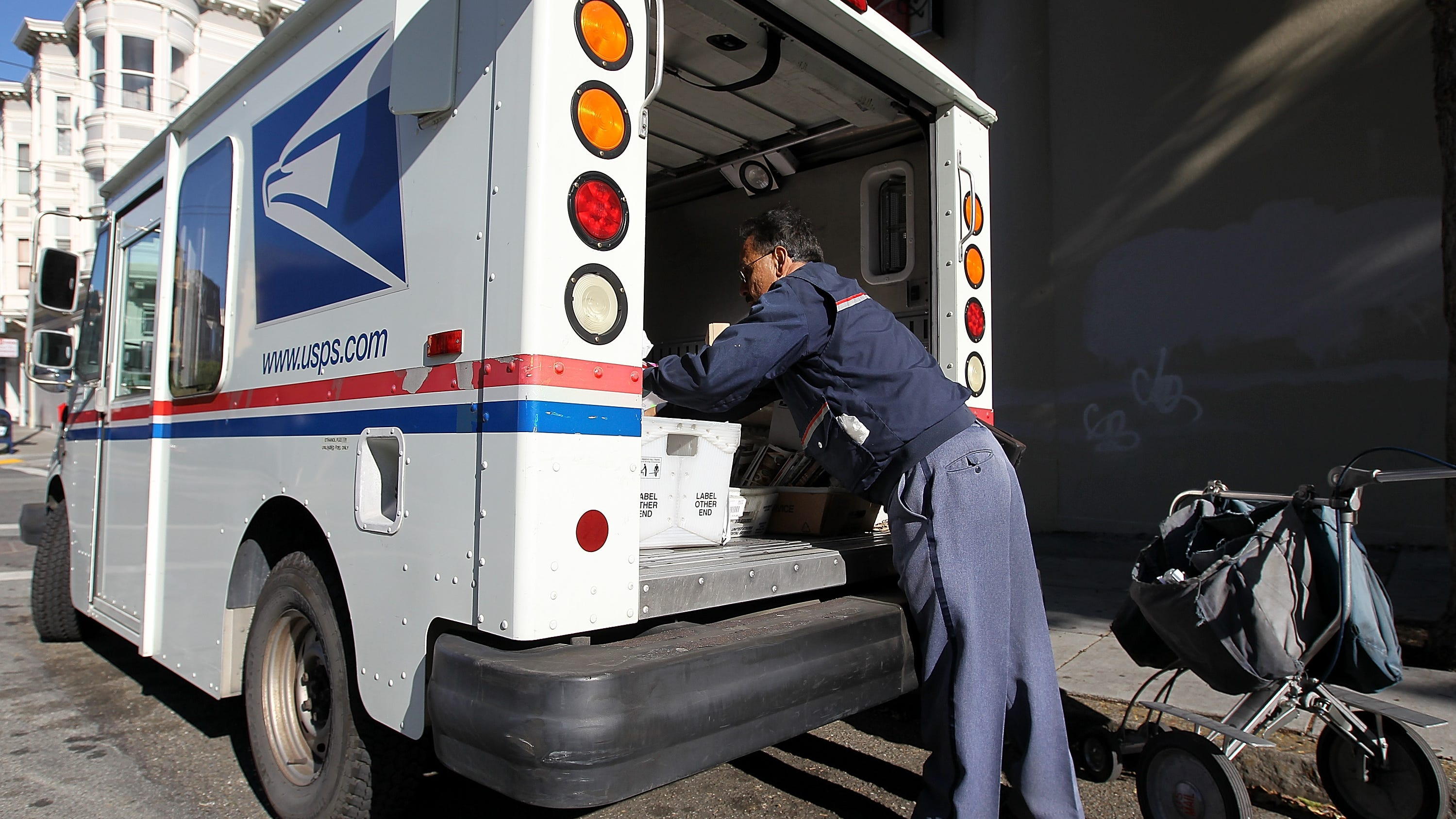 SAN FRANCISCO, CA - DECEMBER 05:  US Postal Service letter carrier Juan Padilla arranges mail in his truck while on his delivery route on December 5, 2011 in San Francisco, California. The US Postal Service announced today that they are considering a plan to eliminate the first class next-day delivery for stamped letters as well as closing half of its 487 mail processing plants across the country in an effort to cut costs and avoid bankruptcy.  (Photo by Justin Sullivan/Getty Images)