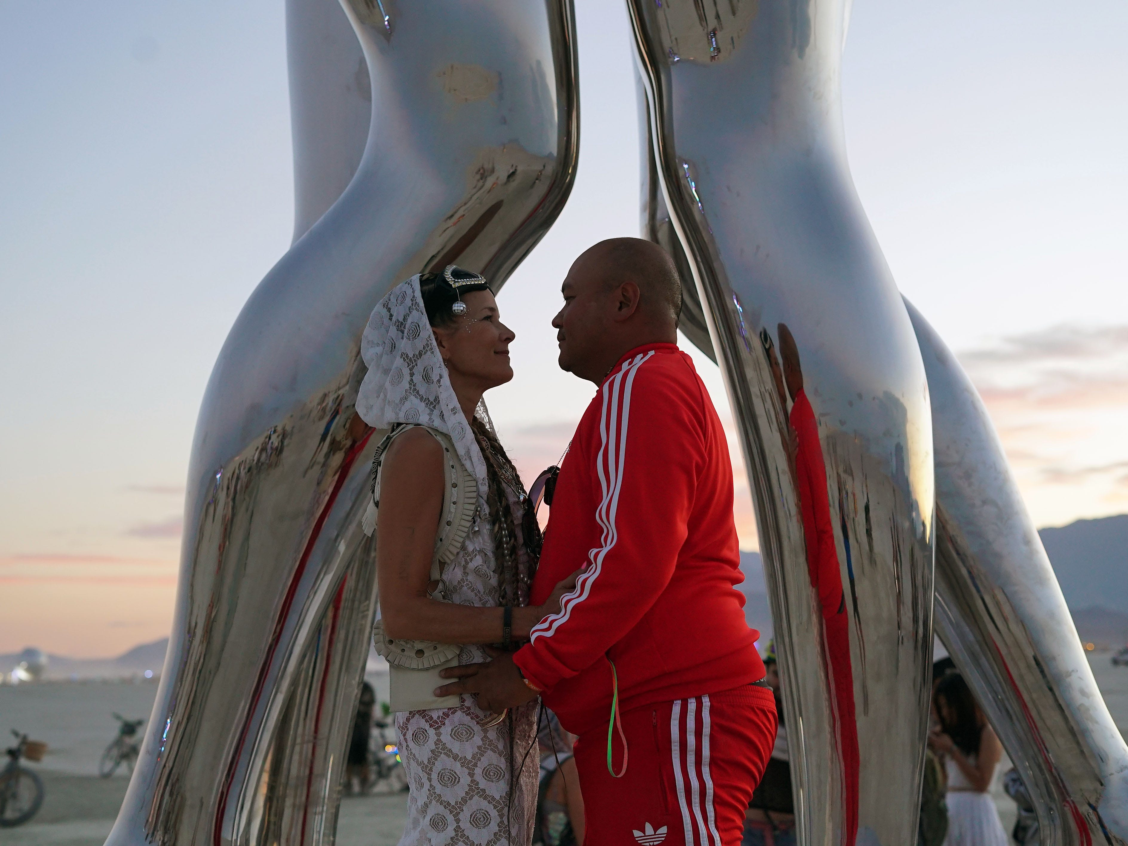 "Cerraeh Laykin and Ryan ""Lushbunny"" Jesena of Los Angeles pause for a moment beneath a polished steel sculpture at Burning Man Aug. 30, 2018. The couple is getting married at the annual event."