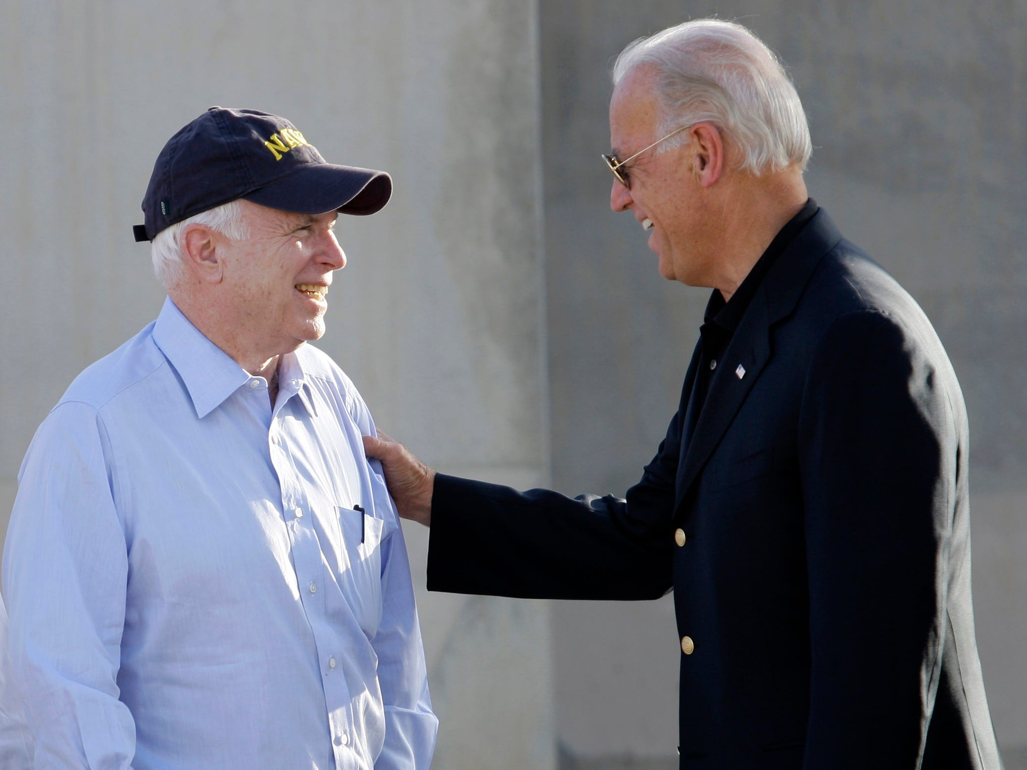 ORG XMIT: BAG105 U.S. Sen. John McCain, left, and Vice President Joe Biden, right, share a light moment after Biden's arrival in Baghdad, Iraq, Saturday, July 3, 2010. Vice President Joe Biden landed Saturday in Baghdad to coax Iraqi leaders into ending their government impasse as vying political factions remain deadlocked over which political bloc should pick its new leaders, including prime minister. High ranking U.S. senators _ Republicans John McCain from Arizona and Lindsey Graham from South Carolina, as well as Joe Lieberman, an independent from Connecticut _ also met Biden at the Baghdad airport on Saturday. They are in Iraq on an unrelated trip and did not travel here with the vice president. (AP Photo/Hadi Mizban)