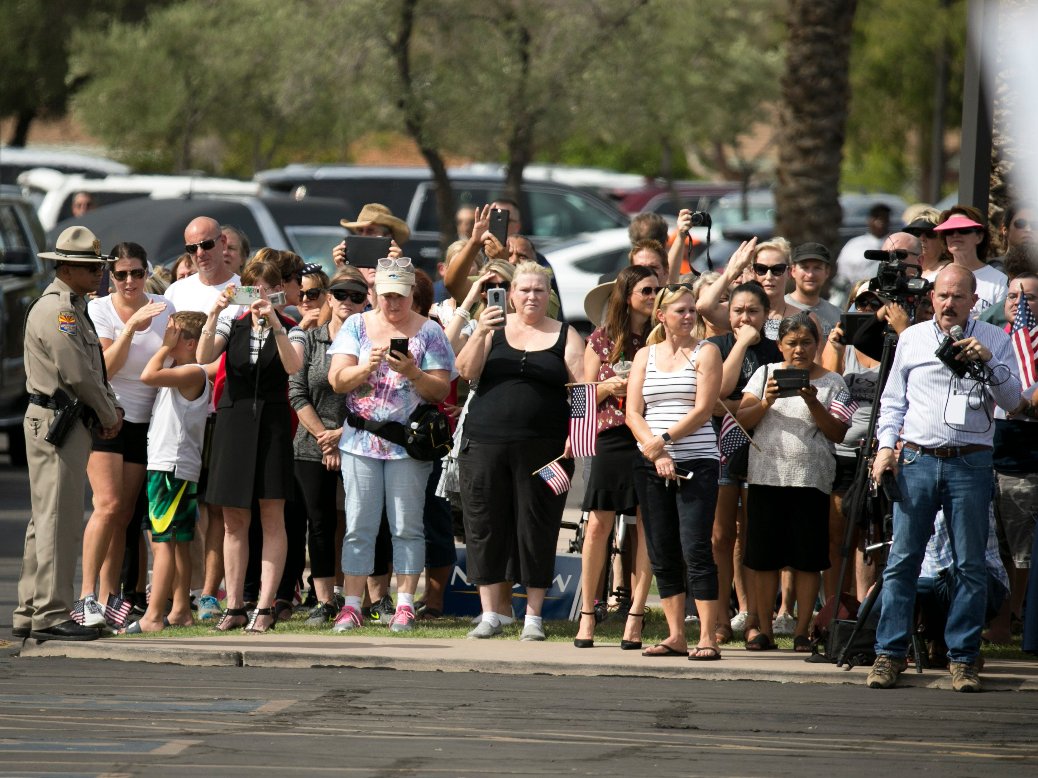 People wait for the motorcade to arrive before a memorial service for Sen. John McCain at North Phoenix Baptist Church in Phoenix, Aug. 30, 2018.