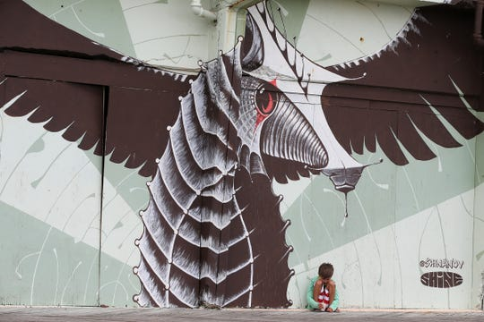 Benji Yazdan, 7, of Maplewood rests against one of the Wooden Wall Project murals on the boardwalk in Asbury Park, NJ Friday August 31, 2018.  He was visiting Asbury Park with his father, David, and aunt, Ariane.