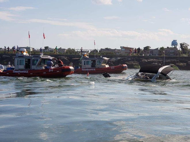 The U.S. Coast Guard and a commercial salvage company assists two boaters whose vessel sank in Barnegat Inlet, New Jersey, August 30th, 2018, . The vessel sank after reportedly striking a jetty, and all persons were safety transferred aboard a Coast Guard vessel from Station Barnegat Light (U.S. Coast Guard photo courtesy of Station Barnegat Light)