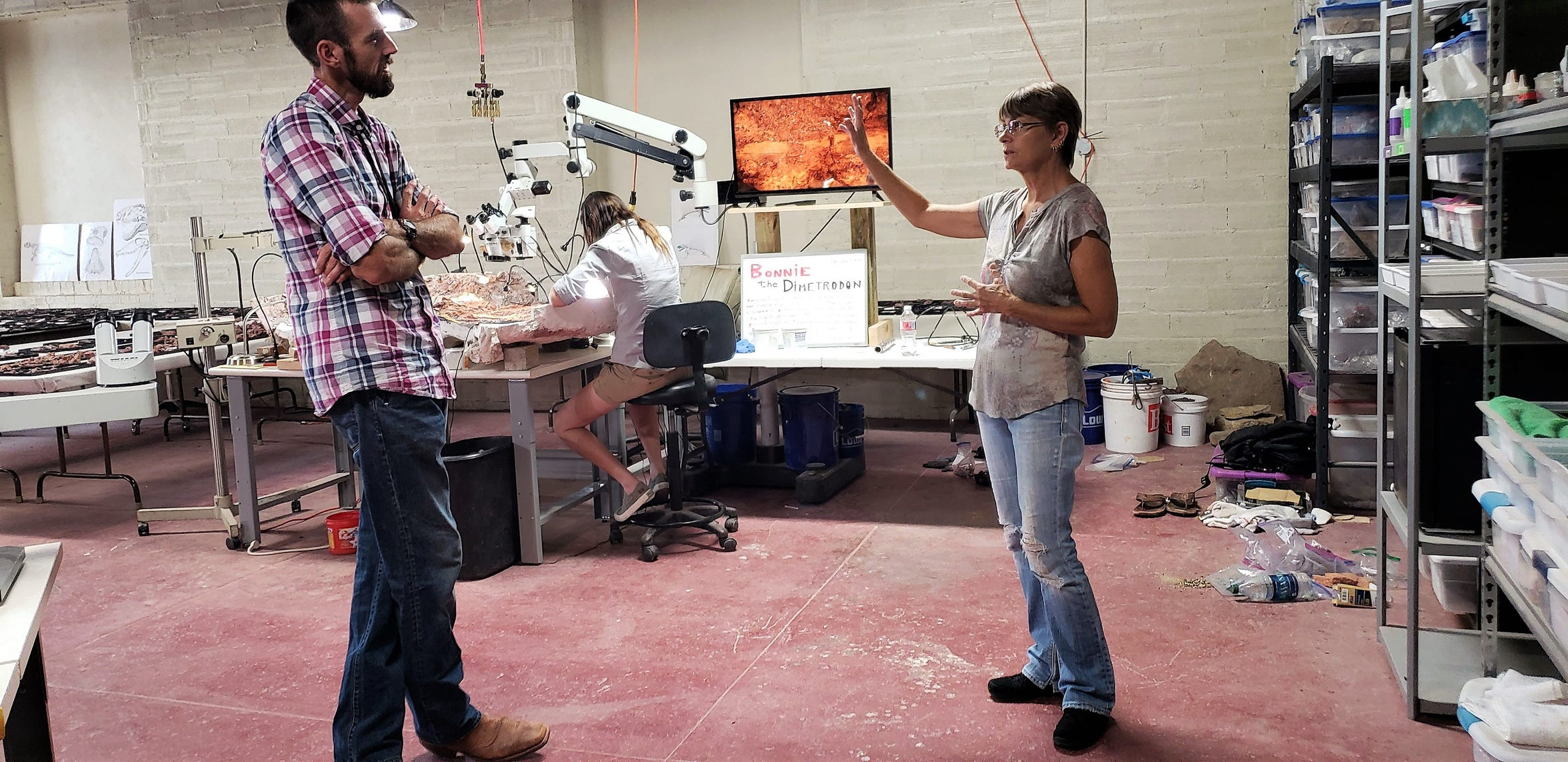 Whiteside museum director Christopher Flis and museum guest Judie Ostlien discuss the museum's open paleontology lab during a recent visit to the museum.