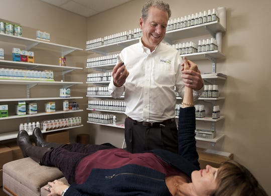 President of Bio King, Dr. Frank King, performs muscle testing on his wife Suzie King as a diagnostic technique in their Asheville facility. Dr. Frank King opened King Bio manufacturing in 1989, turning Asheville into a headquarters for homeopathic medicine with $10 million in revenues.