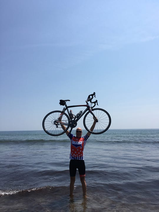 Brad Campbell celebrates his dream of completing a cross-country bicycle trip this past Aug. 6, in Portsmouth, New Hampshire.