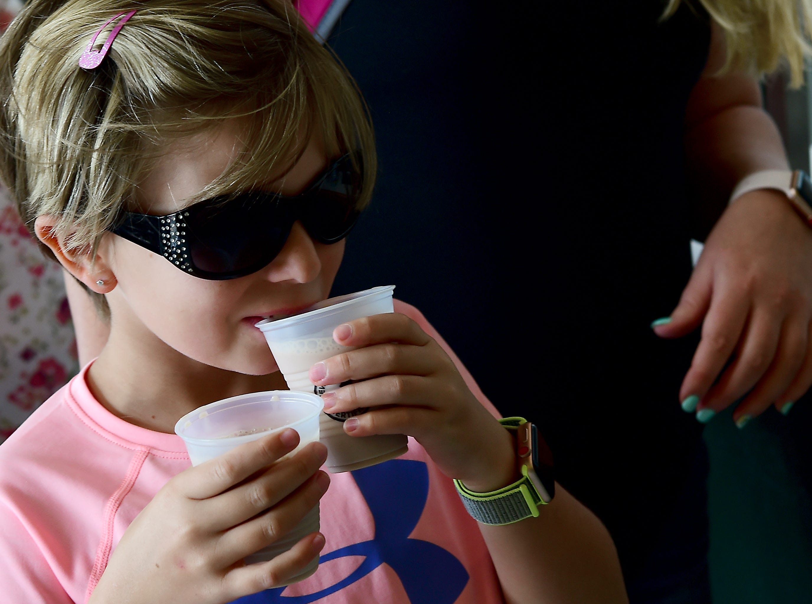 Abby Teeter of Candor enjoys milk from the Milk Bar. The Great New York State Fair is an annual summer tradition that celebrates the agriculture, traditions, foods and people of New York State. The Fair continues through Labor Day at the Fairgrounds near Syracuse, NY. August 30, 2018.