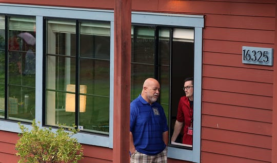 Suquamish Education Department Superintendent Joe Davolos (left) and teacher Jeff Williams chat through the window of Williams's classroom during Chief Kitsap Academy's open house at the new campus in Poulsbo on Aug. 30.
