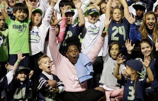 Seattle Seahawks linebacker Shaquem Griffin poses with kids from NubAbility Athletics, a non-profit organization that encourages youth with limb differences to be involved in mainstream sports.