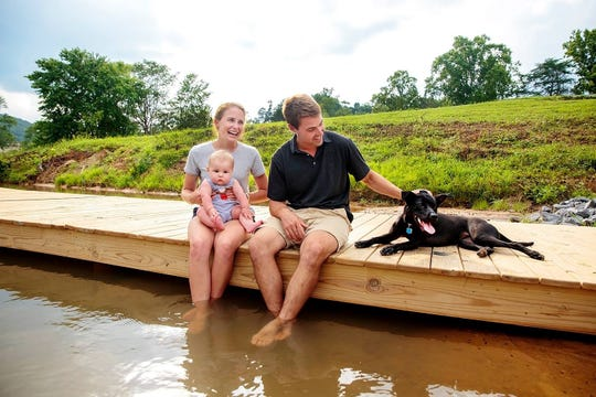 John Menendez and his wife Catherine serve as co-directors of Camp Timberlake, which finished its first summer at its new location in McDowell Co. in August. Joined by their son Peter, the family sits on a dock at the traditional camp they run.