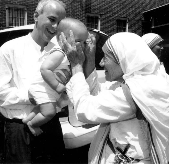 Mother Teresa welcomes a baby as Jim Towey looks on in 1995.