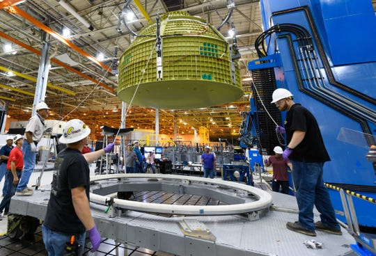 Technicians work on the Orion spacecraft slated for Exploration Mission-2 at NASA's Michoud Assembly Facility near New Orleans, Louisiana.