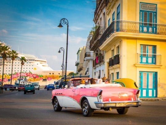 A vintage car drives down a street in Havana, Cuba, with the Norwegian Sun docked at port in the background.