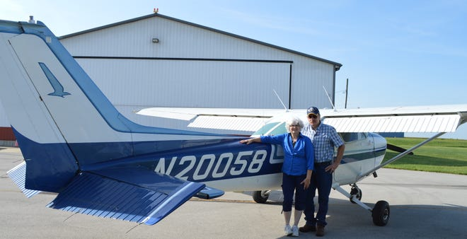 Peg and Sam Ballou stand with one of four planes they own at the Port-Bucyrus Crawford County Airport on Friday morning.