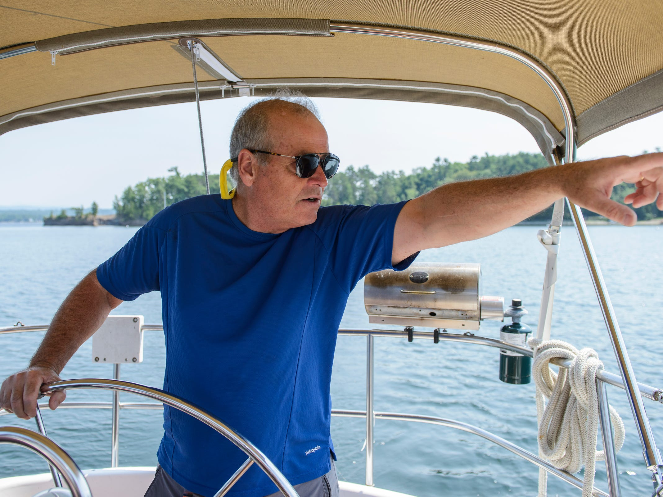 Real Estate agent Chris Von Trapp points to a house during a tour of the waterfront real estate along the shores of Lake Champlain on Friday afternoon August 24, 2018 in Shelburne Bay.