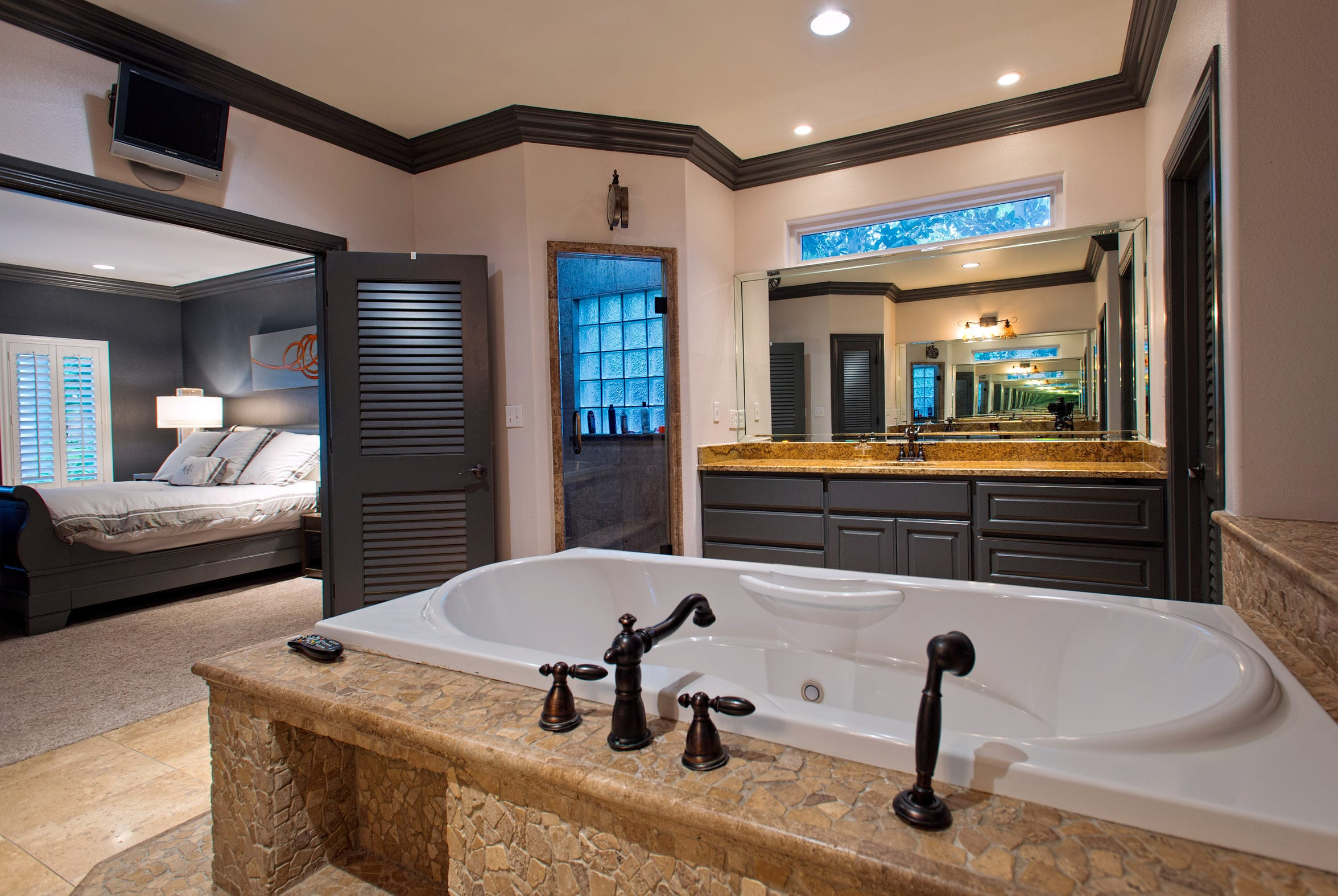 A whirlpool tub is encased in a unique mosaic tile surround in the master bathroom.