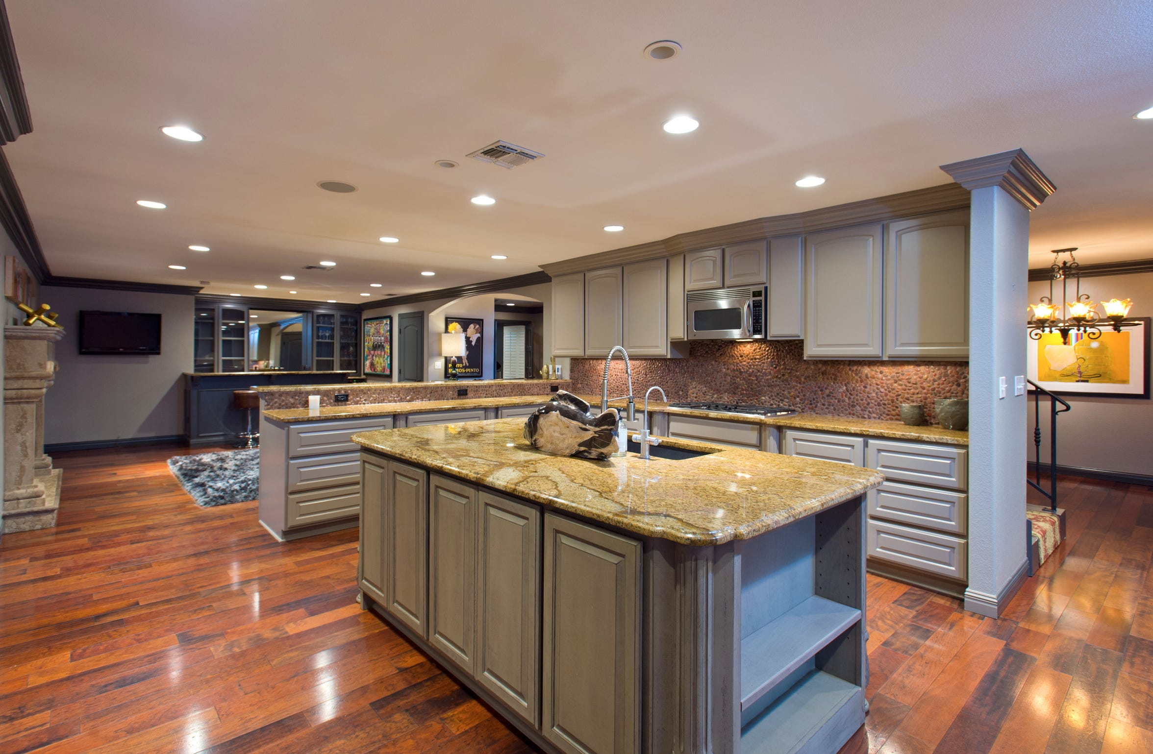 The kitchen is nothing short of amazing with wood flooring, beautiful cabinetry, a granite topped island and counters with a unique pebble back splash.