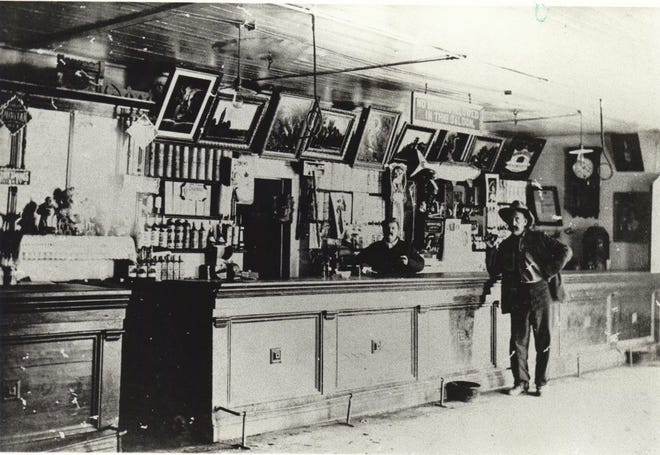 Ben Grande behind the bar serves a customer at the Ben Grande Saloon about 1910.