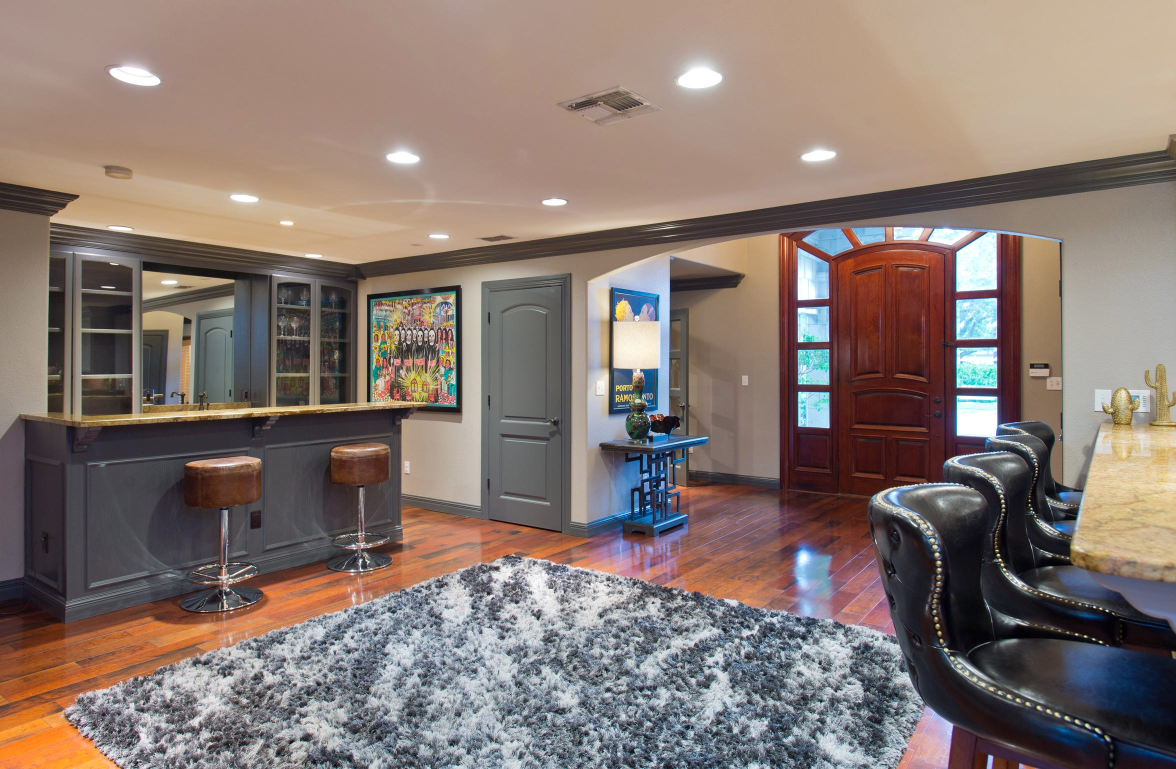 The dramatic entry foyer leads into a bar area that is open to the kitchen.