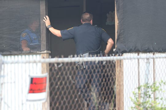 Police talk at the home of an individual who was arrested during a heroin-related warrant roundup.