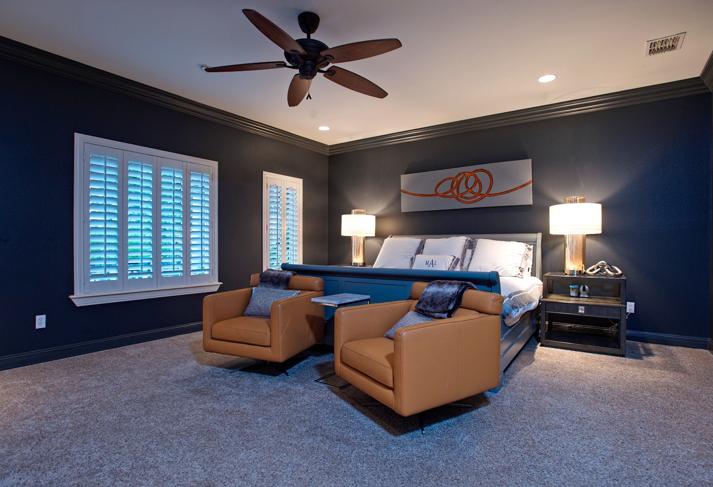 The large master bedroom features plantation shuttered windows,  dark walls and a white ceiling, very relaxing