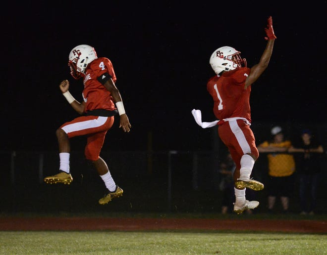 Penns Grove's Tyreke Brown, right, and quarterback Kavon Lewis celebrate a touchdown scored during Thursday night's football game against Pennsville at Penns Grove High School, Aug. 30, 2018.