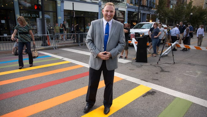 For Video: City Councilman Chris Seelbach, poses for a photo on the new rainbow crosswalk at 12th and Vine Street in Over-the-Rhine. Private donations paid for the makeover and city and county leaders, along with representatives from the LGBTQ helped celebrate the new Pride crosswalk.