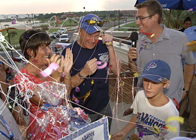 The 200,000th fan Chris Bridges, center, is surprised with confetti by Blue Wahoo staff members as he enters the stadium with his wife, Sharon and son davis Bridges, 9. Blue Wahoos PR and radio announcer Tommy Thrall interviews the family before the game against the Birmingham Barons in 2012.