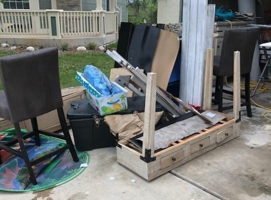 Damaged household goods from the Moseley family's move wait to be hauled away.