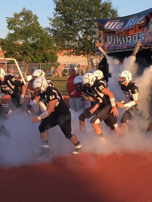 The South Brunswick football team charges to the field before its opener against Lenape on Aug. 30.
