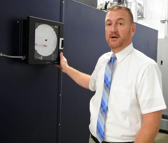 Matt Miller explains one of the gauges on a cremation machine at the new Miller-Kaser Cremation Services on Cedar Street.