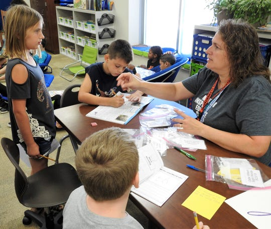 Third-grade teacher Amy Unkefer of Coshocton Elementary School works with students during language arts instruction.