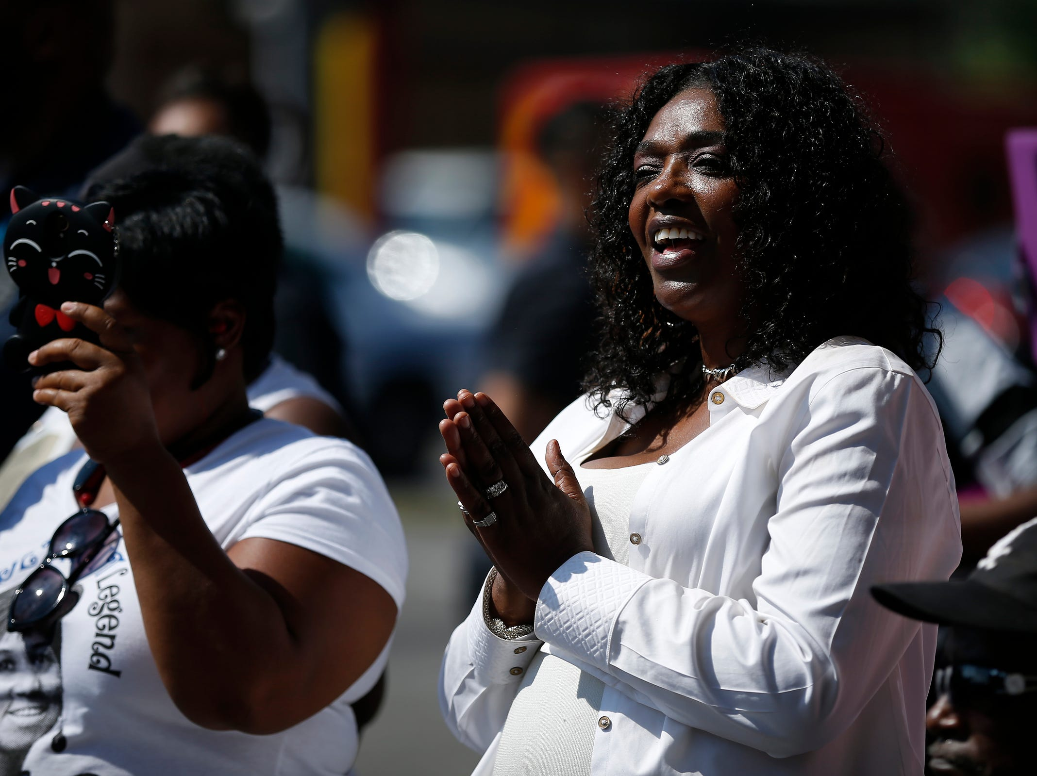 Fans sing along as they watch a live stream of Aretha Franklin's funeral outside of Greater Grace Temple in Detroit on Friday, Aug. 31, 2018.