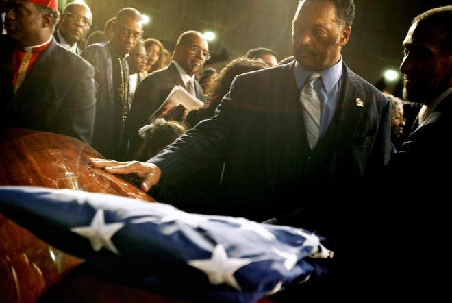 The Rev. Jesse Jackson touches the casket of Rosa Parks before the American flag was draped on the coffin on Wednesday, Nov. 2, 2005, at Greater Grace Temple in Detroit.