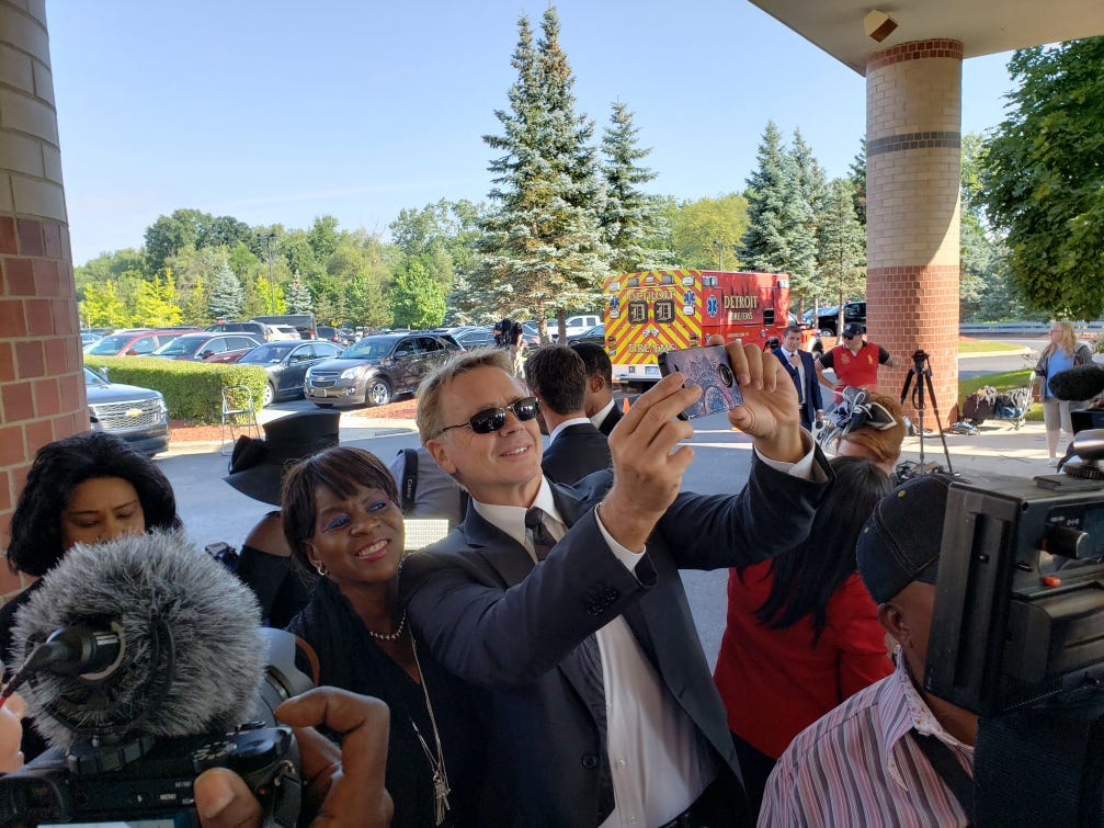 Actor John Schneider takes a photo with a fan while waiting to enter the funeral of Aretha Franklin outside the Greater Grace Temple in Detroit on Friday, Aug. 31, 2018.