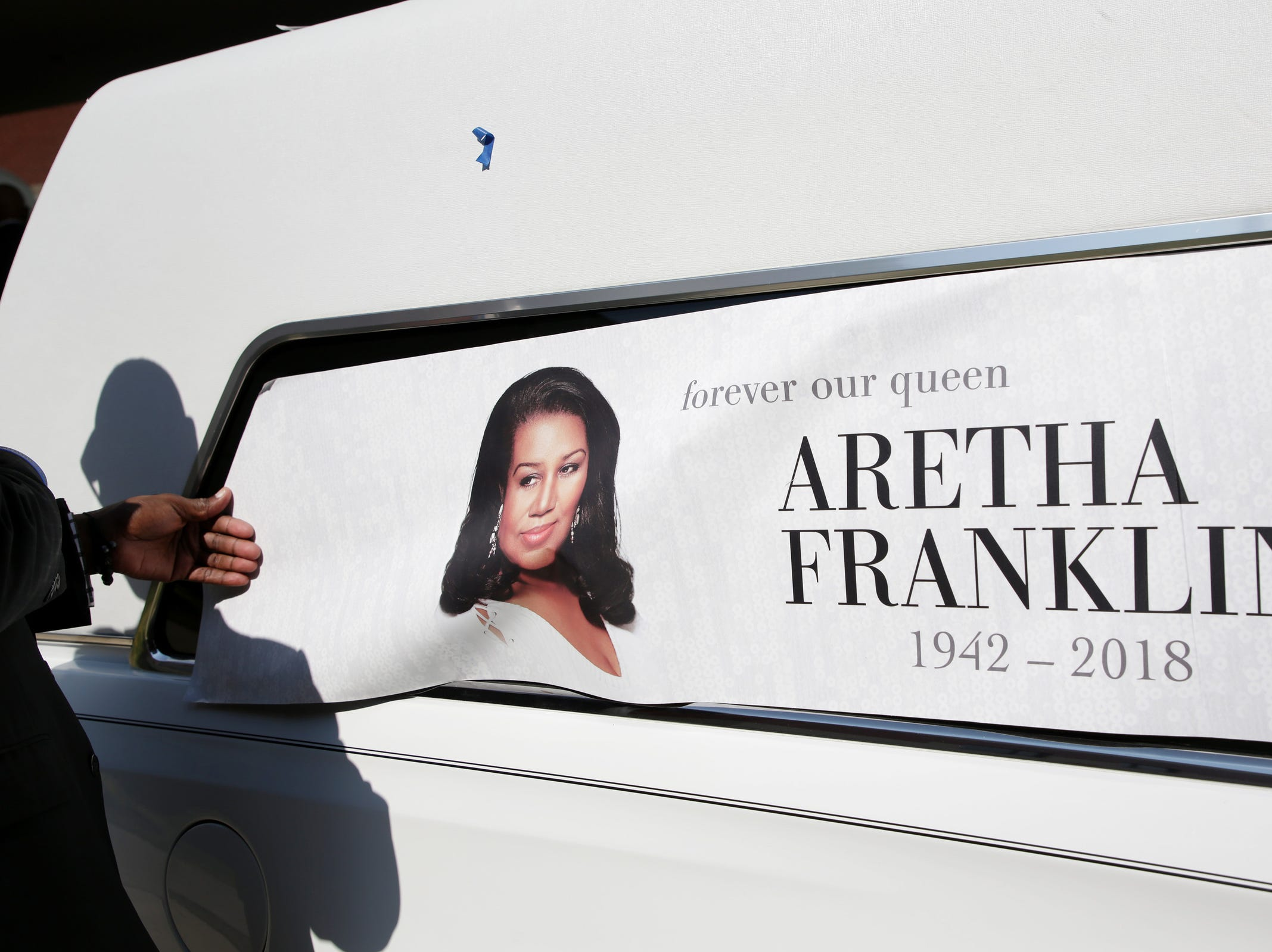 Leon Jones helps applying a removable vinyl in memory of Aretha Franklin on one of the Swanson Funeral Home vehicle during her funeral at Greater Grace Temple on Friday, August 31, 2018.