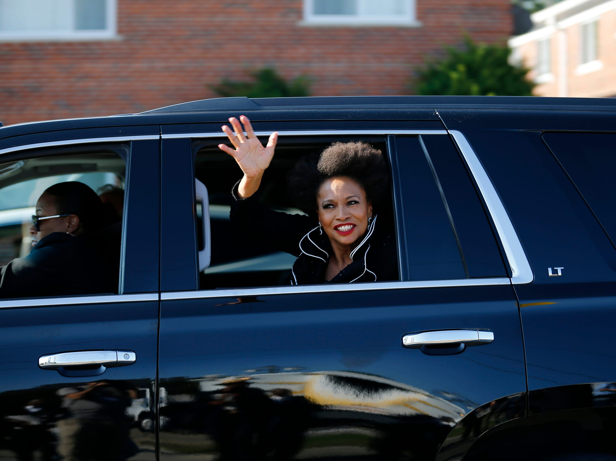 Actress Jenifer Lewis waves to fans as she arrives on Seven Mile Road during the funeral of Aretha Franklin outside the Greater Grace Temple in Detroit on Friday, Aug. 31, 2018.