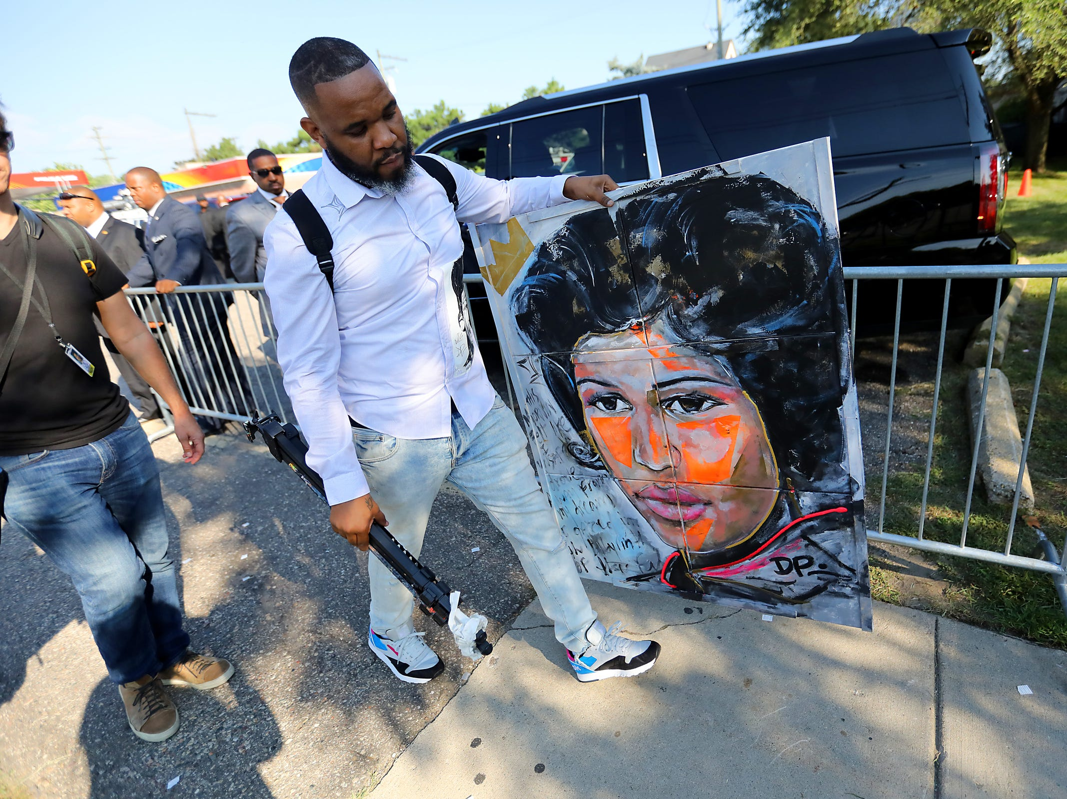 Artist Demont Pinder carries a painting he made of Aretha Franklin inside Greater Grace Temple where people pay their final respects to Aretha Franklin in Detroit on Friday, Aug. 31, 2018.