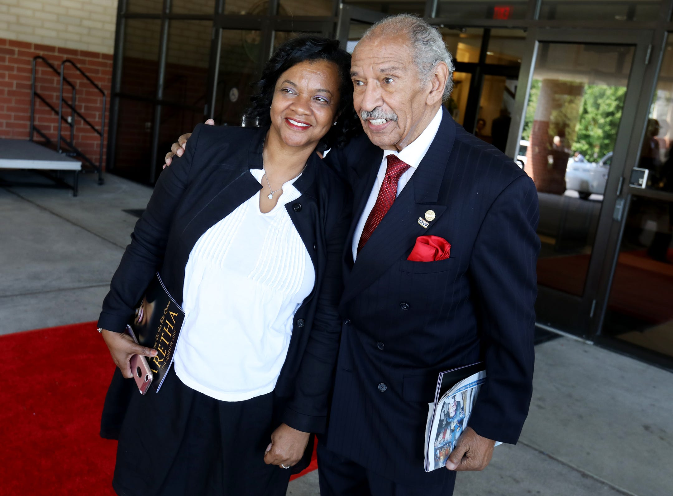 Monica and John Conyers pose for a photograph outside of Aretha Franklin's funeral at Greater Grace Temple in Detroit on Friday, August 31, 2018.